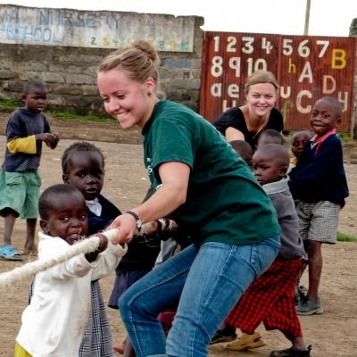 Une volontaire joue en extérieur avec des enfants pendant sa mission humanitaire au Ghana